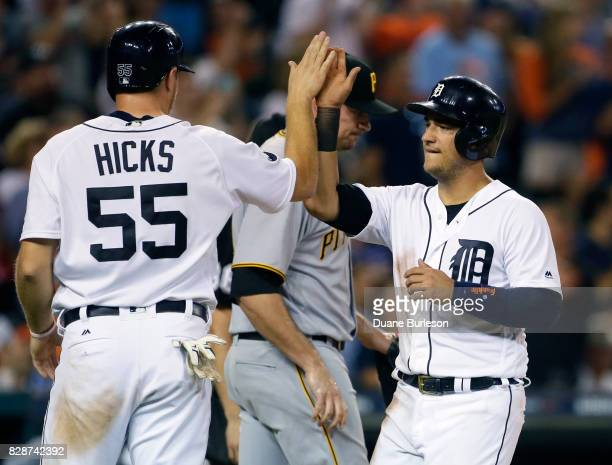 John Hicks of the Detroit Tigers and Jose Iglesias of the Detroit Tigers celebrate after scoring against the Pittsburgh Pirates on a threerun...