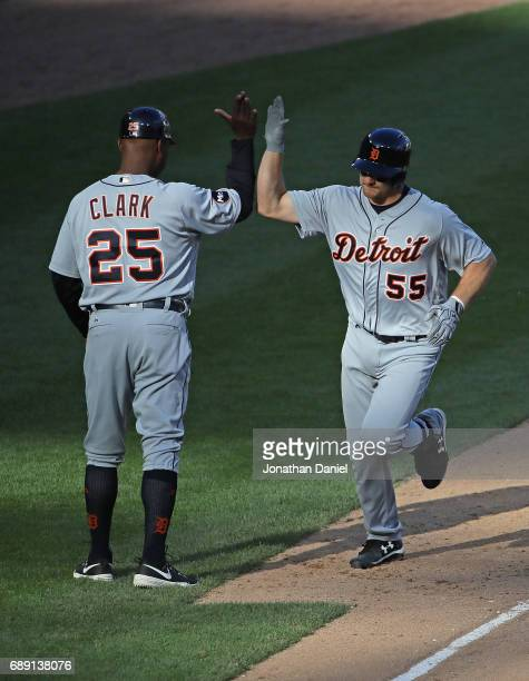 John Hicks of the Detroit Tigers is congratulated by third base coach Dave Clark after hitting a solo home run in the 4th inning against the Chicago...