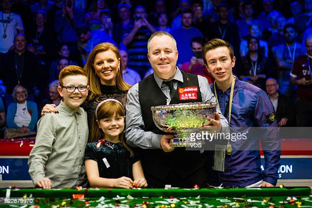 John Higgins of Scotland celebrates with families after winning the final match against Ronnie O'Sullivan of England on day six of Champion of...