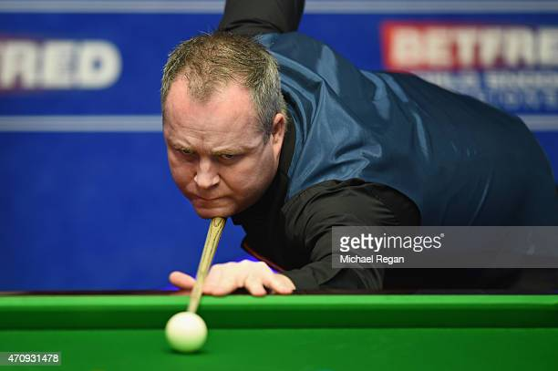 John Higgins of Scotland plays a shot against Ding Junhui of China during day seven of the 2015 Betfred World Snooker Championship at Crucible...