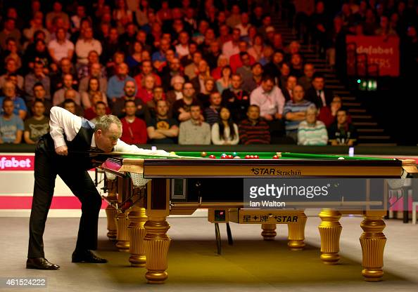 John Higgins of Scotland plays a shot during his first round match against Mark Allen of Northern Ireland on Day Four of the 2015 Dafabet Masters at...