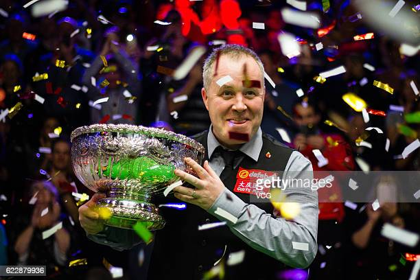 John Higgins of Scotland poses with his trophy after winning the final match against Ronnie O'Sullivan of England on day six of Champion of Champions...