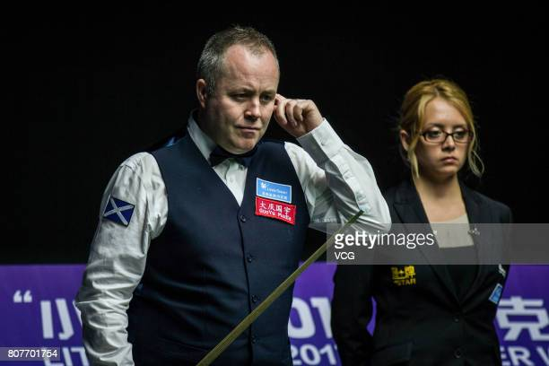 John Higgins of Scotland reacts against Thepchaiya UnNooh of Thailand and Noppon Saengkham of Thailand on day one of 2017 Snooker World Cup at Wuxi...