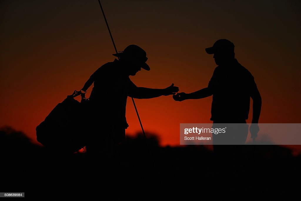 John Huh hands a ball to his caddie during the second round of the Waste Management Phoenix Open at TPC Scottsdale on February 5, 2016 in Scottsdale, Arizona.