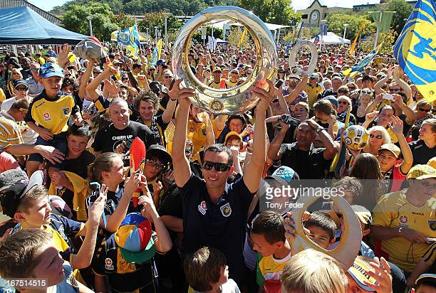 John Hutchinson captain of the Mariners holds the ALeague trophy with fans during the Central Coast Mariners ALeague grand Final celebrations on...