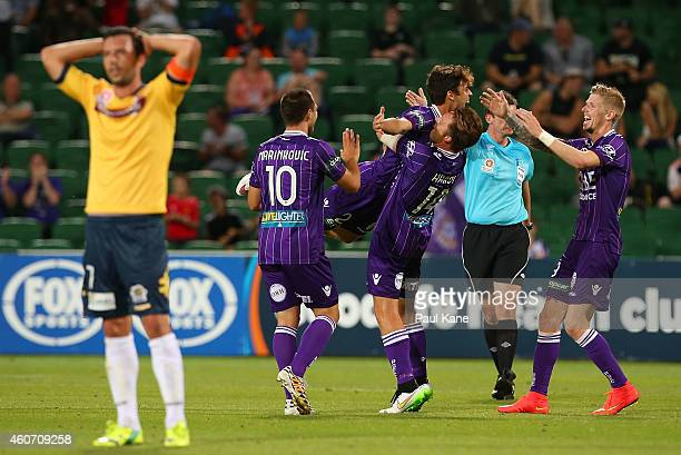 John Hutchinson of the Mariners looks on as Daniel de Silva of the Glory celebrates with team mates after scoring the teams 4th goal during the round...