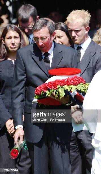 John Hyde father of Lance Corporal Ben Hyde drops a red rose into his son's grave while holding his Royal Military Police hat at his funeral at All...
