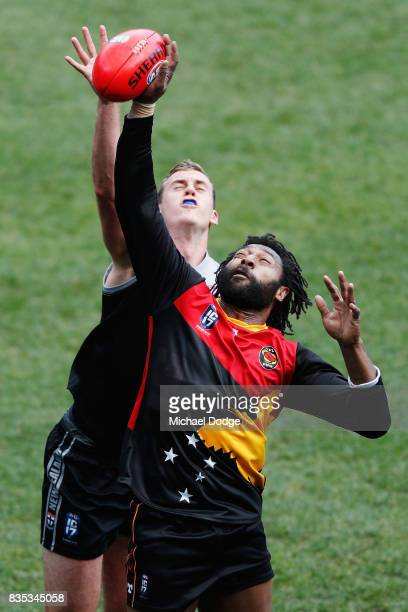 John Ikupu of Papua New Guinea taps the ball from Ty SMITH of New Zealand during the 2017 AFL International Cup Grand FInal match between New Zealand...