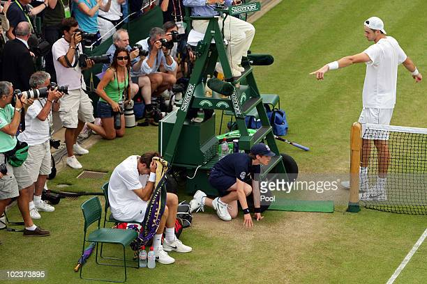 John Isner of USA celebrates winning on the third day of his first round match against Nicolas Mahut of France on Day Four of the Wimbledon Lawn...