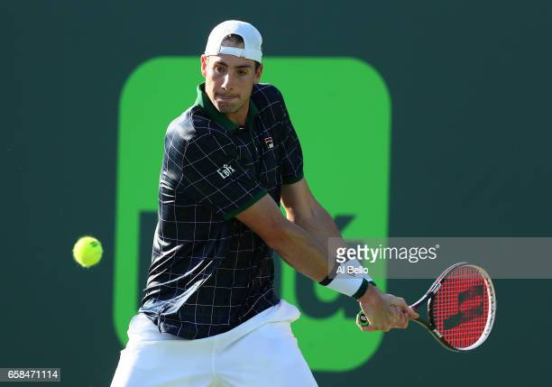 John Isner returns a shot against Alexander Zverev of Germany during Day 8 of the Miami Open at Crandon Park Tennis Center on March 27 2017 in Key...