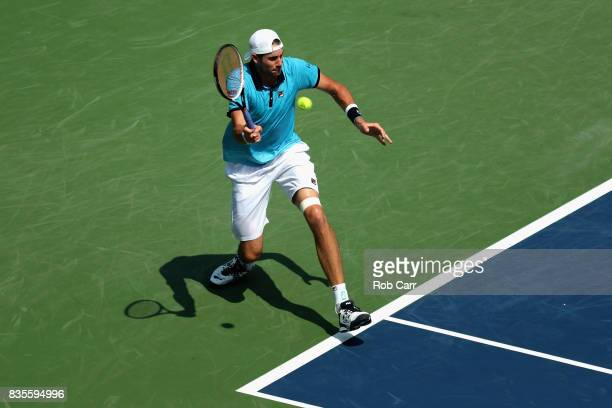 John Isner returns a shot to Grigor Dimitrov of Bulgaria during Day 8 of the Western and Southern Open at the Linder Family Tennis Center on August...