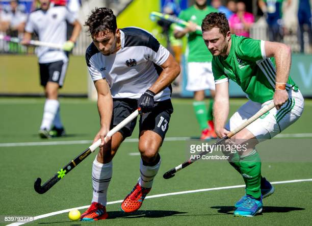 John Jackson of Ireland vies with Benjamin Stanzl of Austria during the hockey semi final match between Ireland and Austria at the Rabo EuroHockey...