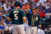 John Jaso of the Oakland Athletics celebrates with Eric Sogard of the Oakland Athletics after hitting a two run home run against the Texas Rangers in...