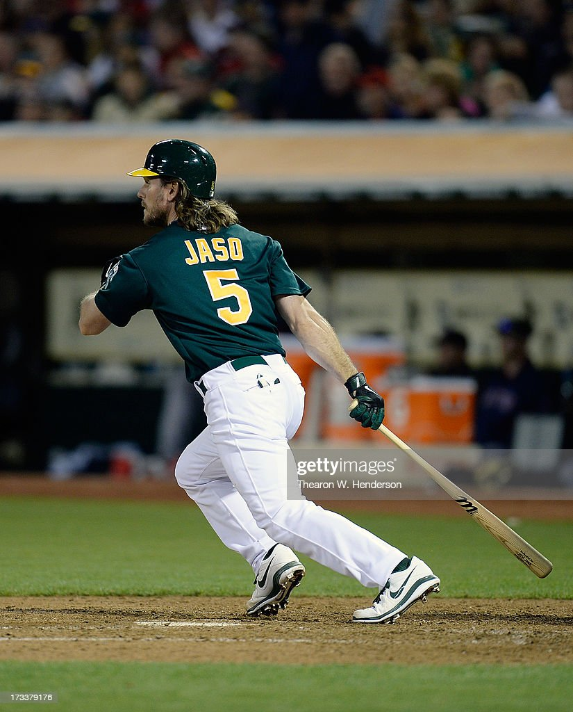 John Jaso #5 of the Oakland Athletics hits an RBI single, scoring Seth Smith (not pictured) in the fifth inning against the Boston Red Sox at O.co Coliseum on July 12, 2013 in Oakland, California.