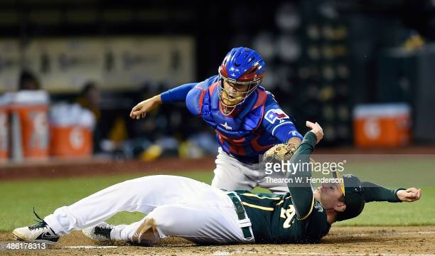 John Jaso of the Oakland Athletics is tagged out at home plate by Robinson Chirinos of the Texas Rangers in the bottom of the second inning at Oco...