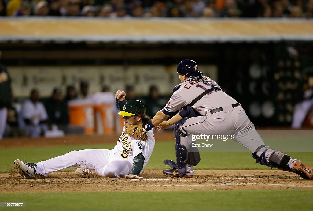 John Jaso #5 of the Oakland Athletics is tagged out by Jason Castro #15 of the Houston Astros in the fifth inning at O.co Coliseum on April 16, 2013 in Oakland, California.