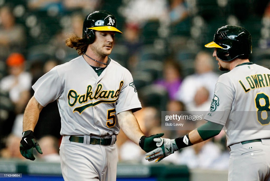 John Jaso #5 of the Oakland Athletics receives congratulations from Jed Lowrie #8 after hitting a home run in the first inning against the Houston Astros at Minute Maid Park on July 24, 2013 in Houston, Texas.