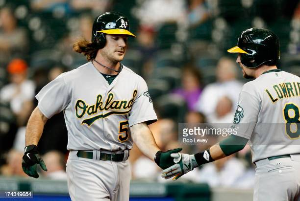 John Jaso of the Oakland Athletics receives congratulations from Jed Lowrie after hitting a home run in the first inning against the Houston Astros...