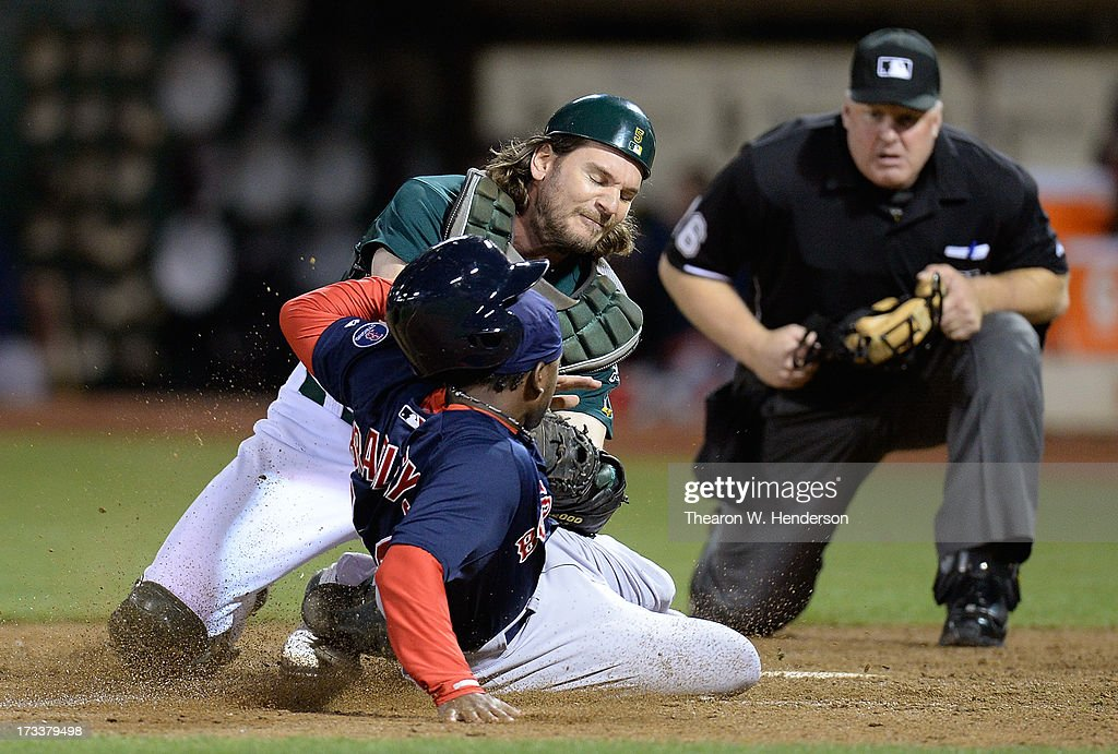 John Jaso #5 of the Oakland Athletics tags out Jackie Bradley Jr #44 of the Boston Red Sox attempting to score on a squeeze play in the ninth inning at O.co Coliseum on July 12, 2013 in Oakland, California. The Red Sox won the game 4-2.