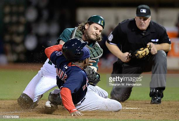 John Jaso of the Oakland Athletics tags out Jackie Bradley Jr of the Boston Red Sox attempting to score on a squeeze play in the ninth inning at Oco...