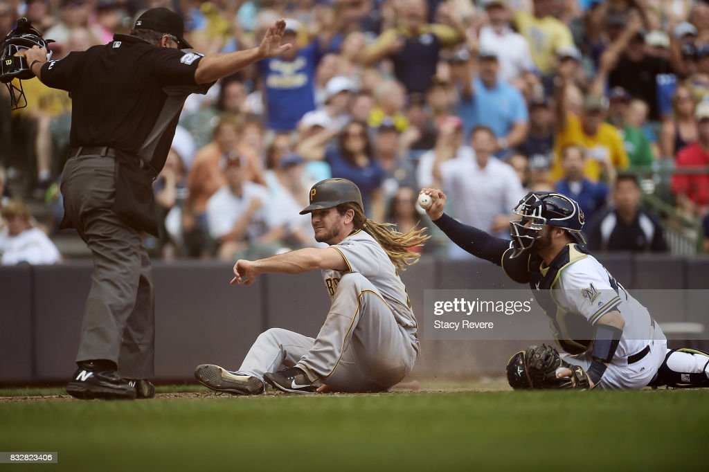 John Jaso #28 of the Pittsburgh Pirates beats a tag at home plate by Manny Pina #9 of the Milwaukee Brewers during the seventh inning of a game at Miller Park on August 16, 2017 in Milwaukee, Wisconsin.