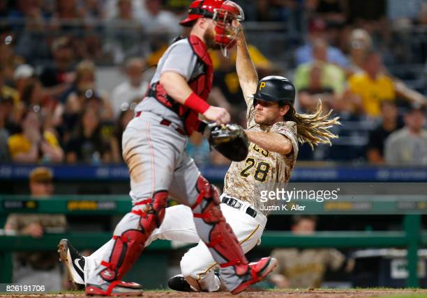 John Jaso of the Pittsburgh Pirates scores on a sacrifice fly in the seventh inning against the Cincinnati Reds at PNC Park on August 3 2017 in...