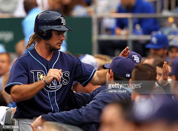 John Jaso of the Tampa Bay Rays is congratulated by teammates in the dugout after scoring during the 3rd inning of the game against the Kansas City...