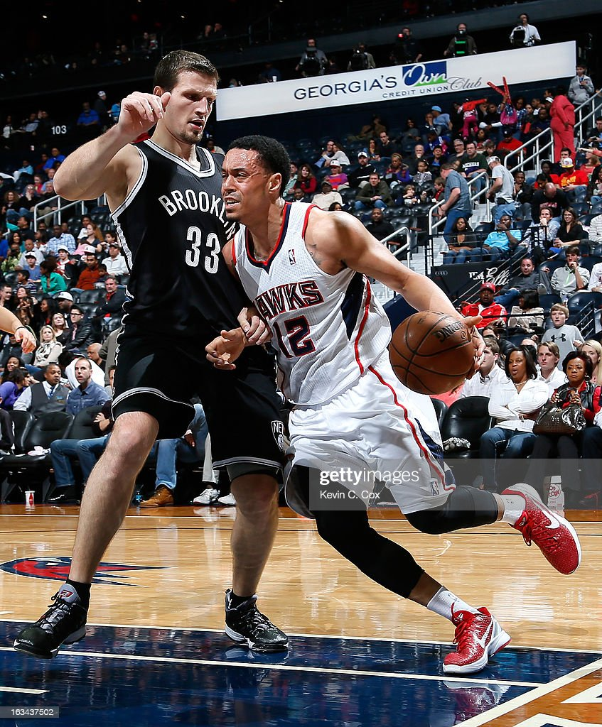 John Jenkins #12 of the Atlanta Hawks drives against Mirza Teletovic #33 of the Brooklyn Nets at Philips Arena on March 9, 2013 in Atlanta, Georgia.