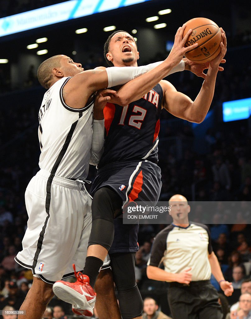 John Jenkins (R) of the Atlanta Hawks goes for a shot against Brooklyn Nets C.J. Watson March 17, 2013 at the Barclay Center in New York. AFP PHOTO / DON EMMERT