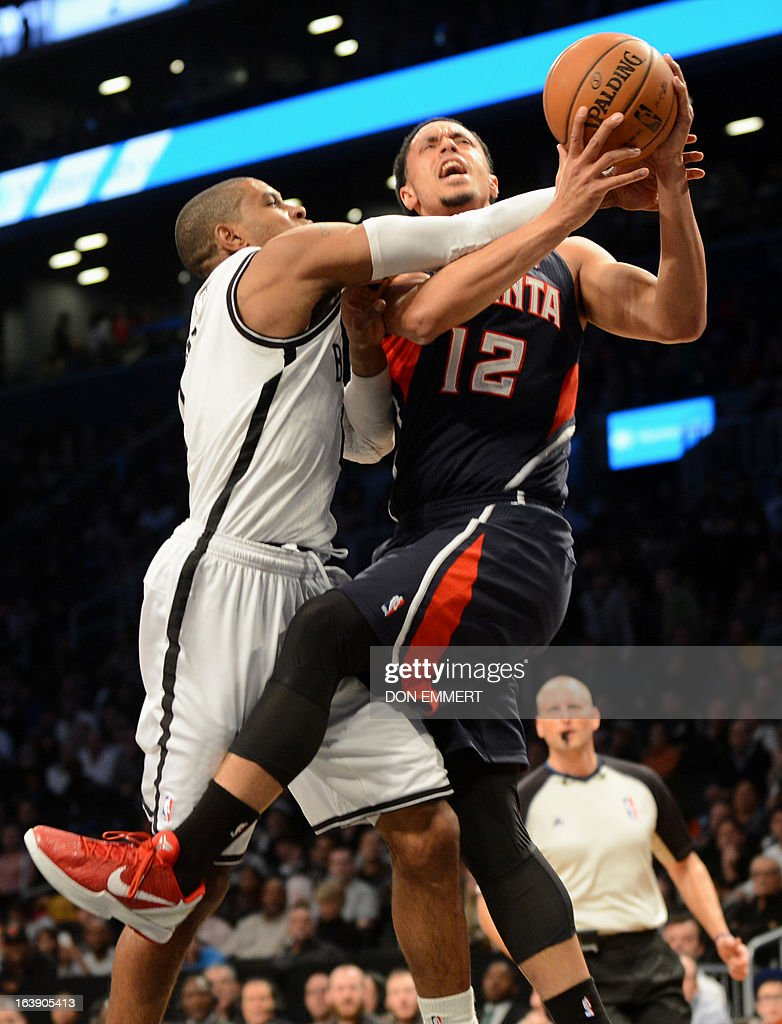 John Jenkins (R) of the Atlanta Hawks goes for a shot against Brooklyn Nets C.J. Watson March 17, 2013 at the Barclay Center in New York.
