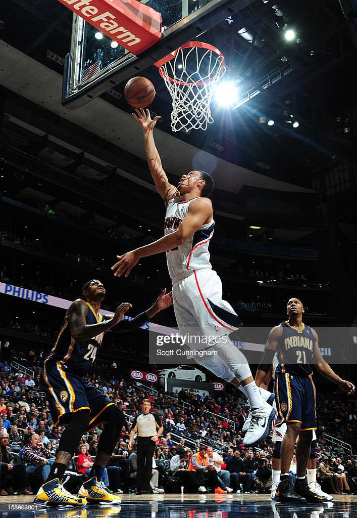 John Jenkins #12 of the Atlanta Hawks rises for a layup against <a gi-track='captionPersonalityLinkClicked' href=/galleries/search?phrase=Paul+George+-+Basketballer&family=editorial&specificpeople=7235030 ng-click='$event.stopPropagation()'>Paul George</a> #24 of the Indiana Pacers on December 29, 2012 at Philips Arena in Atlanta, Georgia.