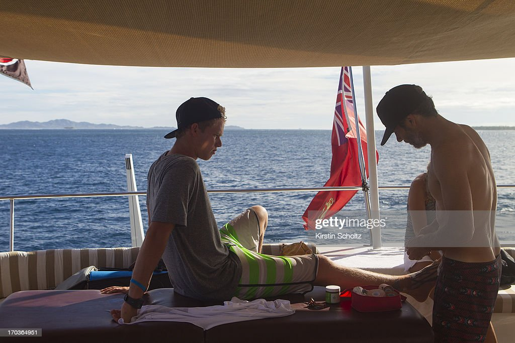 John John Florence gets his foot taped up by the doctor on June 12, 2013 in Tavarua, Fiji.