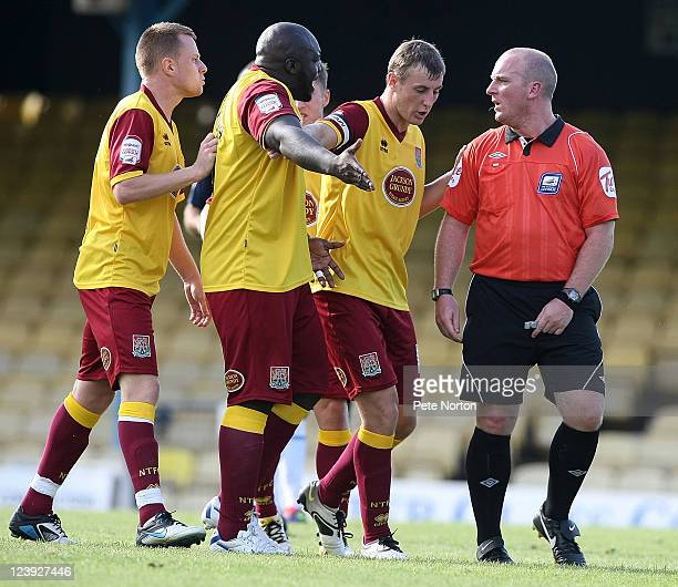 John Johnson of Northampton Town holds back teammate Adebayo Akinfenwa as he makes a point to referee Simon Hooper during the npower League Two match...