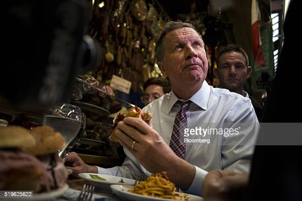 John Kasich governor of Ohio and 2016 Republican presidential candidate pauses while eating a sandwich at Mike's Deli during a campaign stop in the...