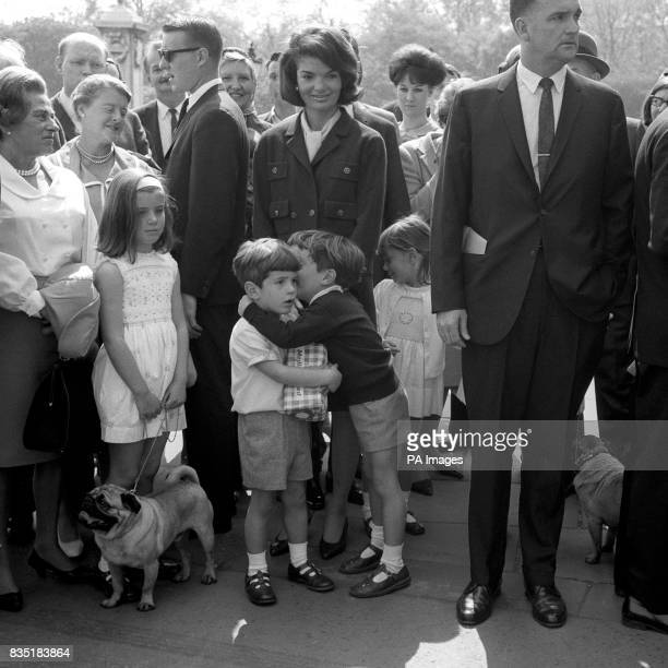 John Kennedy son of the late American President John F Kennedy clutches a loaf to his chest and listens as his cousin Anthony Radziwill takes him...