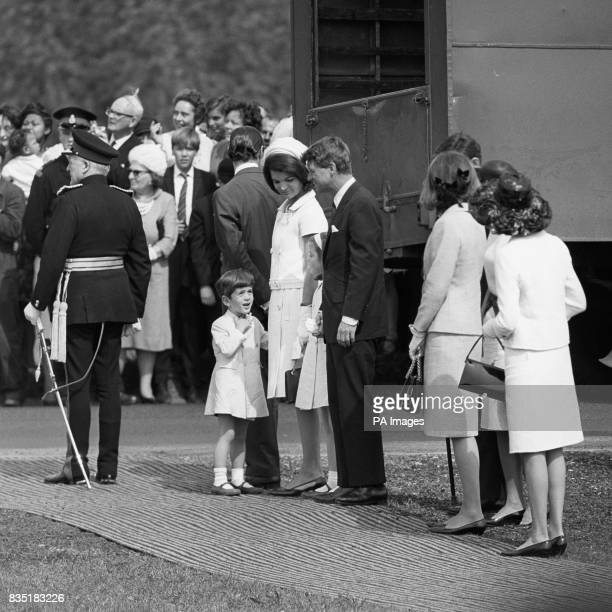 John Kennedy talks with his uncle Senator Robert Kennedy while waiting with his mother Jacqueline Kennedy and sister Caroline to meet Queen Elizabeth...
