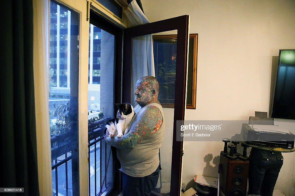 John Kenney and his cat, Lucky Devil look out of the window in his home on April 28, 2016 in Melbourne, Australia. The 60 year old has tattoos all over his body, including his eyelids and eyeballs. His fascination with tattoos started when he was 18, and led to him contracting Hepatitis C from a dirty needle. He even hacked a finger off with a meat cleaver during a part-time job to claim compensation money. After a life of crime on the streets and drug addiction, John Kenney now speaks to school children about the perils of drug abuse and tattoos and is an advocate for the homeless.