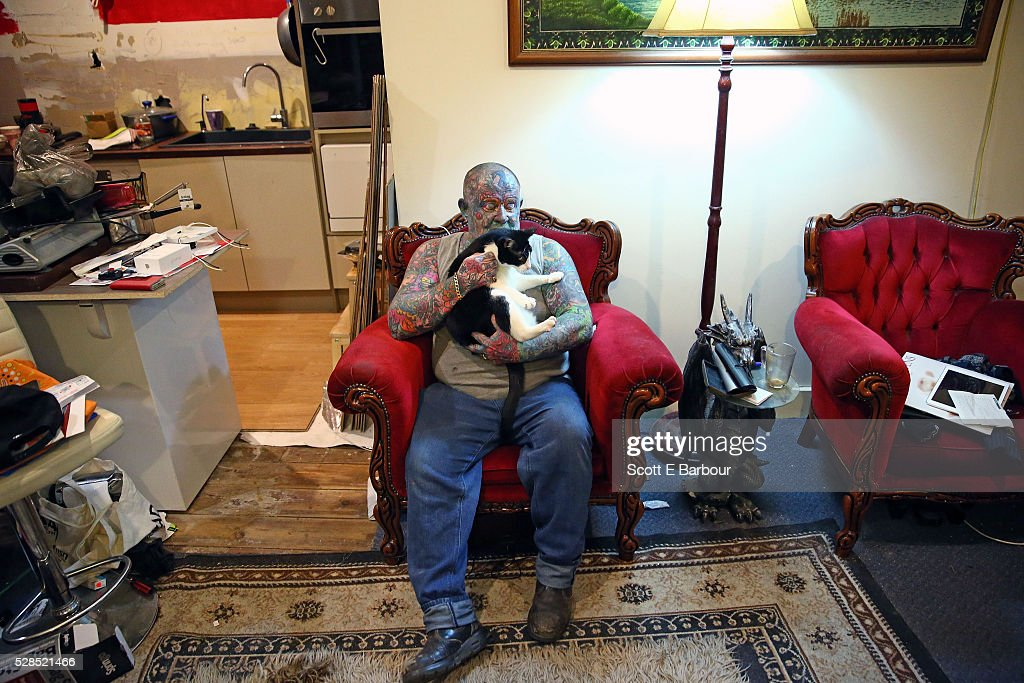 John Kenney hugs his cat, Lucky Devil in his home on April 28, 2016 in Melbourne, Australia. The 60 year old has tattoos all over his body, including his eyelids and eyeballs. His fascination with tattoos started when he was 18, and led to him contracting Hepatitis C from a dirty needle. He even hacked a finger off with a meat cleaver during a part-time job to claim compensation money. After a life of crime on the streets and drug addiction, John Kenney now speaks to school children about the perils of drug abuse and tattoos and is an advocate for the homeless.