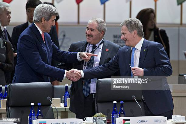 John Kerry US Secretary of State left talks to Sauli Niinisto Finland's president right and Nasser Judeh Jordan's minister of foreign affairs center...