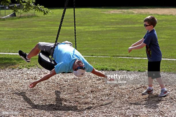 John Killen of Braintree gets a push on the tire swing from his son Jack at Penniman Park in Braintree MA on Aug 8 2017
