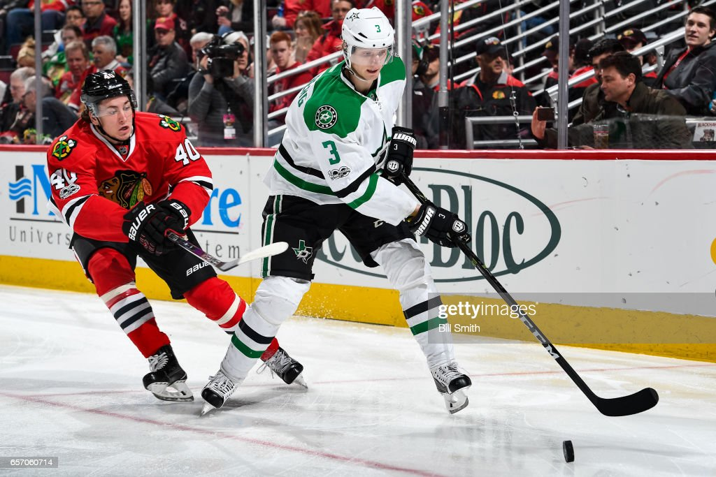 John Klingberg #3 of the Dallas Stars and John Hayden #40 of the Chicago Blackhawks chase the puck in the first period at the United Center on March 23, 2017 in Chicago, Illinois.