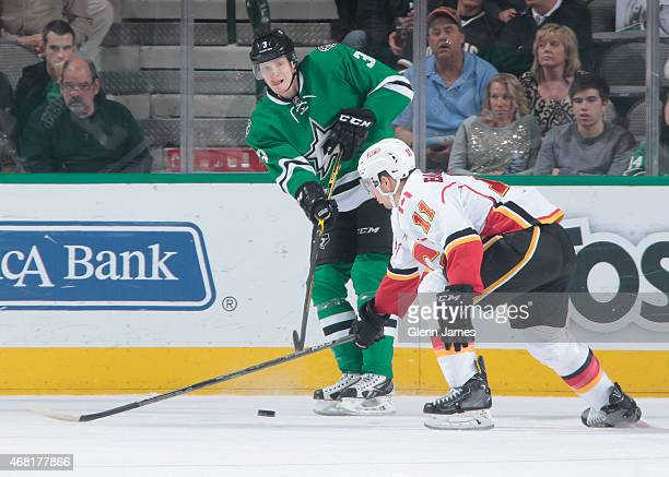 John Klingberg of the Dallas Stars makes a pass to a teammate against Mikael Backlund of the Calgary Flames at the American Airlines Center on March...