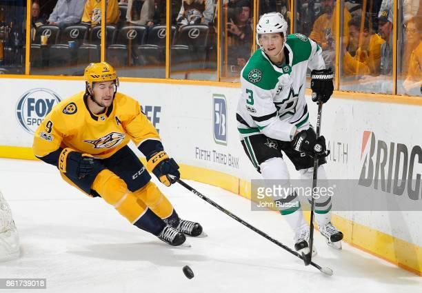 John Klingberg of the Dallas Stars skates against Filip Forsberg of the Nashville Predators during an NHL game at Bridgestone Arena on October 12...