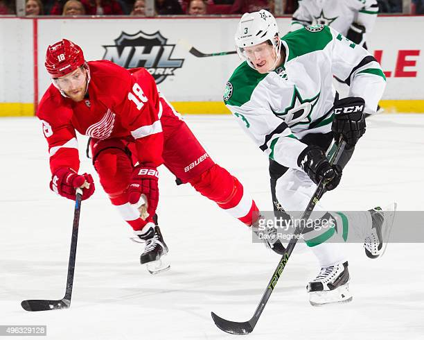 John Klingberg of the Dallas Stars skates with the puck next to Joakim Andersson of the Detroit Red Wings during an NHL game at Joe Louis Arena on...