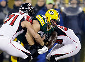 John Kuhn of the Green Bay Packers is tackled by Kroy Biermann of the Atlanta Falcons in the first quarter at Lambeau Field on December 8 2014 in...