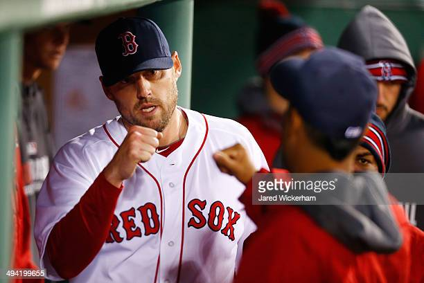 John Lackey of the Boston Red Sox is congratulated by teammates in the dugout after being pulled from the game in the 7th inning by manager John...