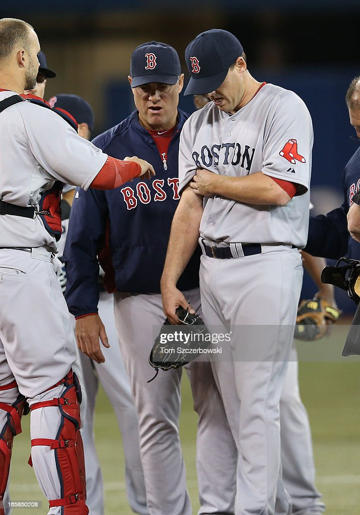 John Lackey #41 of the Boston Red Sox leaves the game in the fifth inning due to an injury to his pitching arm as manager John Farrell #53 looks on at the mound during MLB game action against the Toronto Blue Jays on April 6, 2013 at Rogers Centre in Toronto, Ontario, Canada.