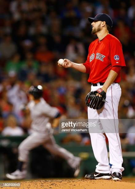 John Lackey of the Boston Red Sox reacts after giving up a home run to Brendan Ryan of the New York Yankees in the third inning during the game on...