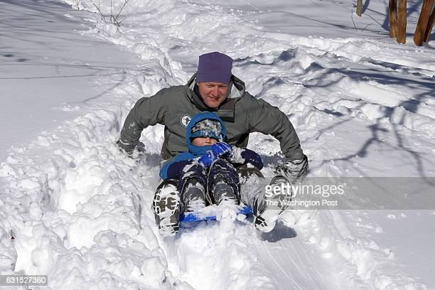 John Lamoreux and his son Reed 5 turning 6yearsold on Monday sled down their front yard after heavy snows crippled the DC area on Sunday January 24...