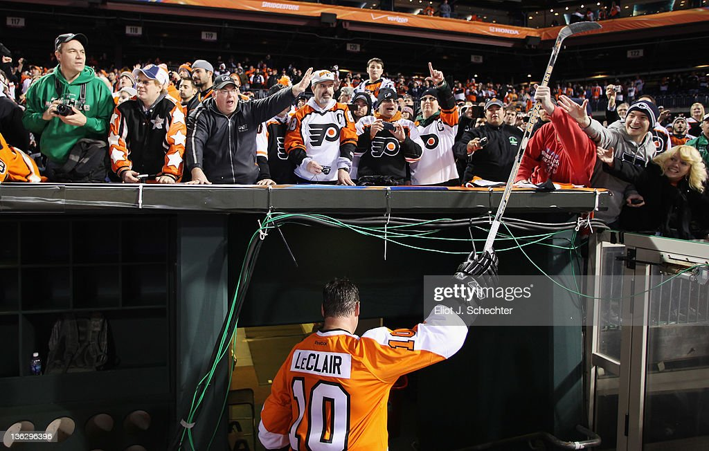 John LeClair #10 of the Philadelphia Flyers hands his stick to a fan after the Alumni Game against the New York Rangers during the on December 31, 2011 in Philadelphia, Pennsylvania.